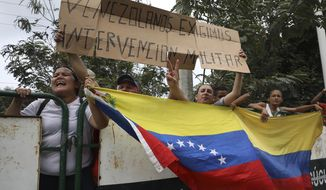 """People hold a Venezuelan flag and the Spanish message: """"Venezuelans demand military intervention,"""" on the sidelines of a visit by U.S. Secretary of State Mike Pompeo in La Parada near Cucuta, Colombia, on the border with Venezuela, Sunday, April 14, 2019. Vice President Mike Pence said on Wednesday, April 10 to the U.N. Security Council that the Trump administration is determined to remove Venezuelan President Nicolas Maduro from power, preferably through diplomatic and economic pressure, but repeated the apparent threat of military action by adding that """"all options are on the table.""""  (AP Photo/Fernando Vergara)"""
