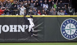 Seattle Mariners center fielder Mallex Smith and fans watch the home run ball of Houston Astros' Jose Altuve in the fifth inning of a baseball game Saturday, April 13, 2019, in Seattle. (AP Photo/Elaine Thompson)