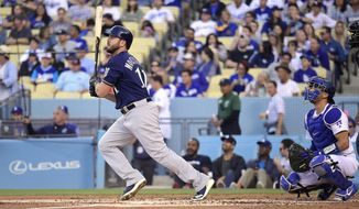 Milwaukee Brewers' Mike Moustakas watches his solo home run next to Los Angeles Dodgers catcher Austin Barnes during the second inning of a baseball game Saturday, April 13, 2019, in Los Angeles. (AP Photo/Mark J. Terrill)