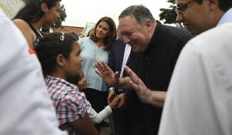 U.S. Secretary of State Mike Pompeo, right, greets a young Venezuelan migrant at a migrant shelter, as he's given a tour by Colombian Vice President Marta Lucia Ramirez, behind, and Colombian President Ivan Duque, not in picture, in La Parada near Cucuta, Colombia, on the border with Venezuela, Sunday, April 14, 2019. Pompeo is on a four-day Latin American tour, making his final stop at the Colombian border to meet with representatives of Venezuelan refugees. (AP Photo/Fernando Vergara)