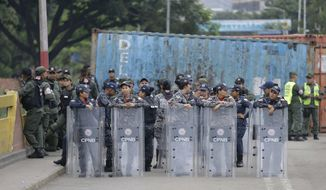 Female Venezuelan soldiers stand behind their shields on the Simon Bolivar International Bridge, where cargo trailers block it, seen from La Parada near Cucuta, Colombia, on the border with Venezuela, Sunday, April 14, 2019. Venezuelan authorities have limited the use of the bridge to students, seniors and the sick. U.S. Secretary of State Mike Pompeo is on a four-day Latin American tour, making his final stop at the Colombian border to meet with representatives of Venezuelan refugees. (AP Photo/Fernando Vergara)