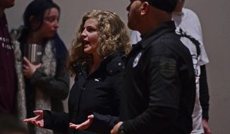 Protester Kaitlin Bennett is escorted out of the auditorium by police before Sen. Bernie Sanders, I-Vt., speaks at an Ohio workers town hall meeting, Sunday, April 14, 2019, in Warren, Ohio. (AP Photo/David Dermer)