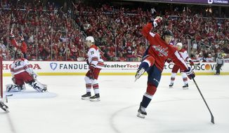 Washington Capitals right wing T.J. Oshie, right, celebrates his goal against Carolina Hurricanes goaltender Petr Mrazek (34), of the Czech Republic, and center Sebastian Aho (20), of Finland, during the first period of Game 2 of an NHL hockey first-round playoff series, Saturday, April 13, 2019, in Washington. The Capitals won 4-3 in overtime. (AP Photo/Nick Wass) ** FILE **