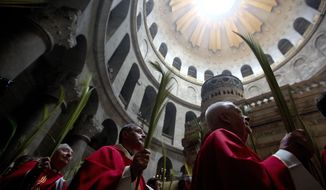 Catholic priests carry palm fronds at the Church of the Holy Sepulchre, traditionally believed by many Christians to be the site of the crucifixion and burial of Jesus Christ, in Jerusalem's old city, Sunday, April 14, 2019. Palm Sunday marks for Christians, Jesus Christ's entrance into Jerusalem, when his followers laid palm branches in his path, prior to his crucifixion. (AP Photo/Sebastian Scheiner)