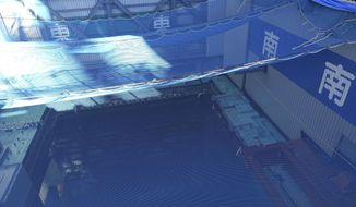 In this Jan. 25, 2018, file photo,a cooling pool where a total of mostly used 566 sets of fuel rods are stored underwater and covered by a protective net, waits to be removed in a step to empty the pool at Unit 3 of the Fukushima Dai-ichi nuclear power plantahead ofa fuel removal from its storage poolin Okuma, Fukushima Prefecture, northeast Japan. (AP Photo/Mari Yamaguchi, File)