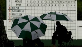 Patrons watch from under umbrellas during the second round for the Masters golf tournament Friday, April 12, 2019, in Augusta, Ga. (AP Photo/Charlie Riedel)
