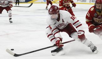 Massachusetts defenseman Cale Makar (16) controls the puck during the second period in a semifinal against Denver during the Frozen Four NCAA men's college hockey tournament Thursday, April 11, 2019, in Buffalo, N.Y. (AP Photo/Jeffrey T. Barnes)