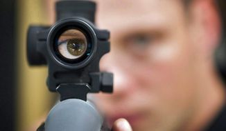 FILE - In this Sept. 15, 2010 file photo, an employee looks through the scope of long gun at a gun store in Calgary, Alberta, Canada. When Canada first sought to restrict gun access in the 1990s, the National Rifle Association threatened a boycott by U.S. hunters spending tourism dollars in the country. (Jeff McIntosh/The Canadian Press via AP)