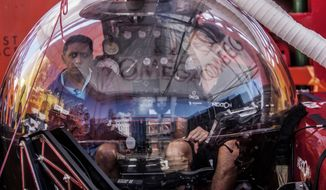 In this Saturday, April 13, 2019, photo, Seychelles President Danny Faure, left, sits inside a submersible on the deck of vessel Ocean Zephyr, off the coast of Desroches, in the outer islands of Seychelles. Faure toured the vessel and was presented with some of the findings and observations made by a British-led science expedition documenting changes taking place beneath the waves that could affect billions of people in the surrounding region over the coming decades. (AP Photo/Steve Barker)