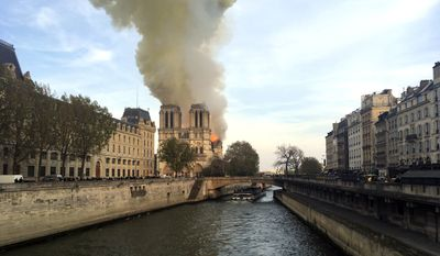 Notre Dame cathedral is burning in Paris, Monday, April 15, 2019. Massive plumes of yellow-brown smoke is filling the air above Notre Dame Cathedral and ash is falling on tourists and others around the island that marks the center of Paris. (AP Photo/Lori Hinant)