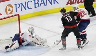 Carolina Hurricanes' Warren Foegele (13) scores against Washington Capitals goalie Braden Holtby (70) while Capitals' Lars Eller (20) defends during the second period of Game 3 of an NHL hockey first-round playoff series in Raleigh, N.C., Monday, April 15, 2019. (AP Photo/Gerry Broome)