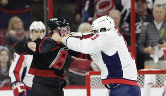 Washington Capitals' Alex Ovechkin, right, of Russia, punches Carolina Hurricanes' Andrei Svechnikov, also of Russia, during the first period of Game 3 of an NHL hockey first-round playoff series in Raleigh, N.C., Monday, April 15, 2019. (AP Photo/Gerry Broome)