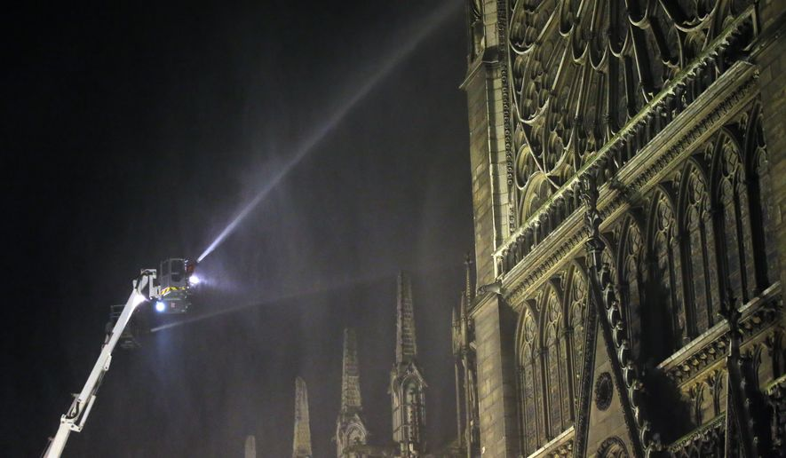 Firefighters spray water onto Notre Dame cathedral as it burns in Paris, Monday, April 15, 2019. Massive plumes of yellow brown smoke is filling the air above Notre Dame Cathedral and ash is falling on tourists and others around the island that marks the center of Paris. (AP Photo/Michel Euler)