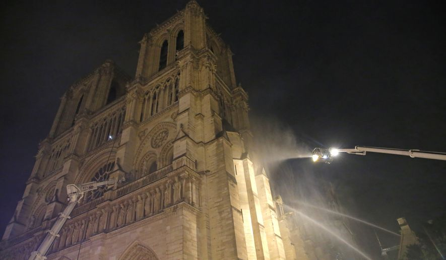 Firefighters spray water onto the facade of Notre Dame cathedral to stop the spread of a fire in Paris, Monday, April 15, 2019. Massive plumes of yellow brown smoke is filling the air above Notre Dame Cathedral and ash is falling on tourists and others around the island that marks the center of Paris. (AP Photo/Michel Euler)