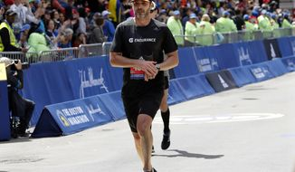 NASCAR driver Jimmie Johnson, of Charlotte, N.C., finishes the 123rd Boston Marathon on Monday, April 15, 2019, in Boston. (AP Photo/Winslow Townson)