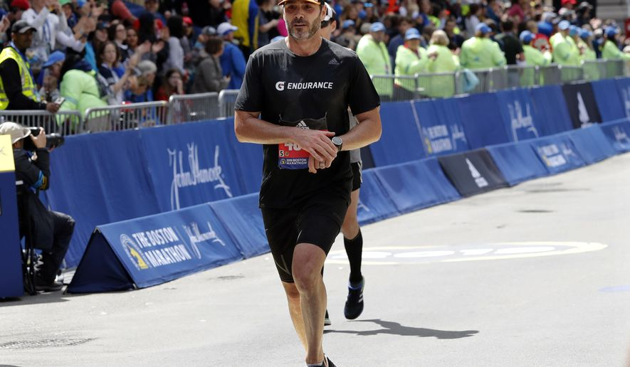 NASCAR driver Jimmie Johnson, of Charlotte, N.C., finishes the 123rd Boston Marathon on Monday, April 15, 2019, in Boston. (AP Photo/Winslow Townson)