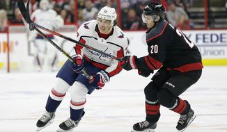 Carolina Hurricanes' Sebastian Aho (20), of Finland, and Washington Capitals' T.J. Oshie (77) chase the puck during the first period of Game 3 of an NHL hockey first-round playoff series in Raleigh, N.C., Monday, April 15, 2019. (AP Photo/Gerry Broome) ** FILE **