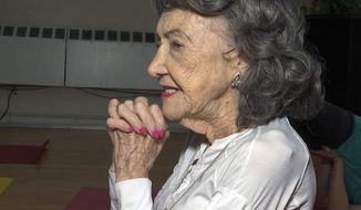 In this April 5, 2019, image made from a video, 100-year-old Tao Porchon-Lynch teaches a yoga class in Hartsdale, N.Y. (AP Photo/Ted Shaffrey)