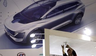 A worker installs lightings before the start of the Auto Shanghai 2019 show in Shanghai on Monday, April 15, 2019. This year's Shanghai auto show which starts Thursday highlights the global industry's race to make electric cars Chinese drivers want to buy as Beijing winds down subsidies that promoted sales. (AP Photo/Ng Han Guan)