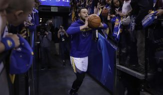 In this Sunday, April 7, 2019, photo, Golden State Warriors' Stephen Curry shoots from the players' entrance tunnel prior to the team's NBA basketball game against the Los Angeles Clippers in Oakland, Calif. Curry's pregame tunnel heaves have become such a spectacle at Oracle Arena hundreds of cameras raise in the air to capture the moment. He won't have that anymore at Chase Center when the Warriors move across the bay to San Francisco next season. (AP Photo/Ben Margot)