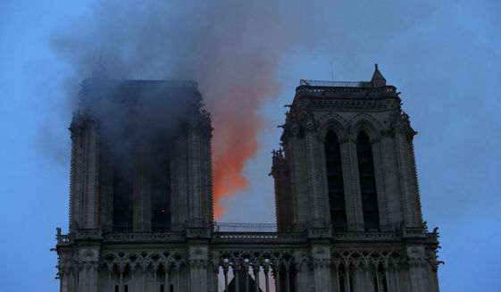 Smoke and flames fill the sky as a fire burns at the Notre Dame Cathedral during the visit by French President Emmanuel Macron in Paris, Monday, April 15, 2019. A catastrophic fire engulfed the upper reaches of Paris' soaring Notre Dame Cathedral as it was undergoing renovations Monday, threatening one of the greatest architectural treasures of the Western world as tourists and Parisians looked on aghast from the streets below.(Philippe Wojazer/Pool via AP)