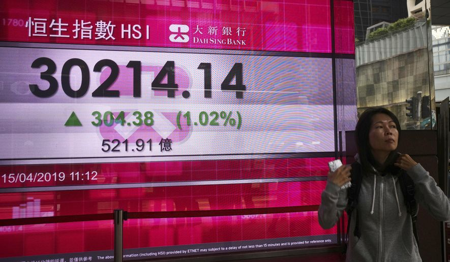 A woman walks past an electronic board showing Hong Kong share index outside a local bank in Hong Kong, Monday, April 15, 2019.  Asian markets were broadly higher Monday on signs that the U.S. and China were closing in on a trade deal after months of negotiations.(AP Photo/Vincent Yu)