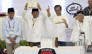 In this Sept. 21, 2018, file photo, Indonesian presidential candidates Prabowo Subianto, second from left, and his running mate Sandiaga Uno, left, Joko Widodo, second from right, and his running mate Ma'ruf Amin, show the ballot numbers that will represent them in the upcoming presidential election, during a draw at the General Election Commission office in Jakarta, Indonesia. (AP Photo/Achmad Ibrahim, File)