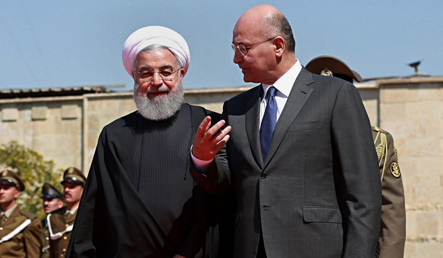 In this March 11, 2019, file photo, Iraqi President Barham Salih, right, walks with visiting Iranian President Hassan Rouhani, before their meeting at Salam Palace in Baghdad, Iraq. Iraq is seeking to reclaim a leadership role in the Arab world after decades of conflict. It is focusing on a centrist policy and its top leaders are determined to maintain good relations with both Iran and the United States. (AP Photo/Khalid Mohammed, File)