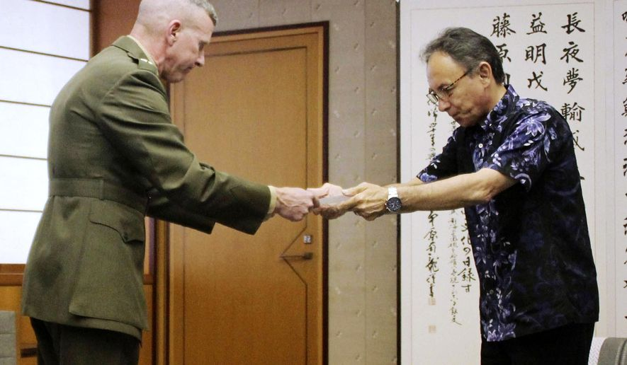 Okinawa Gov. Denny Tamaki, right, hands out a letter of protest to Lt. Gen. Eric Smith, U.S. Marines commander in Japan, at Okinawa Prefectural Government Office in Naha, Okinawa, Japan, Monday, April 15, 2019. The commander is asking service people on the southwestern region of Okinawa to keep a low profile to show respect after a sailor allegedly stabbed a Japanese woman and then killed himself. (Kyodo News via AP)