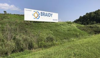 File-This Aug. 22, 2018, file photo shows a sign declaring the future home of Braidy Industries' aluminum mill in Ashland, Ky. An aluminum company planning to build a $1.7 billion plant in Appalachia is forming a partnership with a Russian company that until recently faced U.S. sanctions. Russian aluminum giant Rusal wants to invest $200 million in an aluminum rolling mill that Braidy Industries intends to build near Ashland, Kentucky. Rusal says it would assume a 40 percent ownership share in the mill in return for the investment. Braidy Industries would hold the other 60 percent share. (AP Photo/Adam Beam, File)