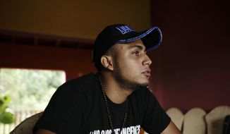 """FILE - In this July 28, 2018 file photo, Jairo Bonilla, leader of the April 19 student movement, wearing a T-shirt designed with a hashtag that reads in Spanish: """"We are not criminals,"""" during an interview in Managua, Nicaragua. """"For us as exiles there is no guarantee that we could return and nothing would happen to us."""" said Bonilla, Monday, 15, 2019 who now lives in Costa Rica, in response to Nicaragua's government announcement that it will implement a program to guarantee the safe return of exiles. (AP Photo/Arnulfo Franco, File)"""