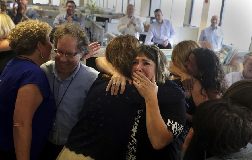 Staff of the South Florida Sun Sentinel celebrate their bittersweet honor Monday, April 15, 2019, in Deerfield Beach, Fla., after winning the Pulitzer Prize for Public Service. The newspaper won for its coverage of the Parkland school shooting. (Carline Jean/South Florida Sun-Sentinel via AP)