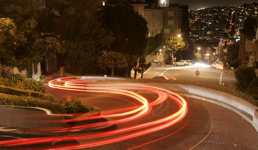 FILE - In this April 28, 2008 file photo, motorists wind their way down Lombard Street in San Francisco. Tourists may soon have to pay a fee to drive down San Francisco's world-famous crooked street. California officials plan to announce a proposal Monday, April 15, 2019 that would grant San Francisco permission to establish a toll and reservation system. (AP Photo/Marcio Jose Sanchez, File)