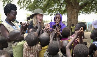 In this photo taken Tuesday, April 2, 2019, human rights activist Mia Farrow, center-left, plays a game with children during a visit to an internally displaced person's camp in the capital Juba, South Sudan. (AP Photo/Sam Mednick)