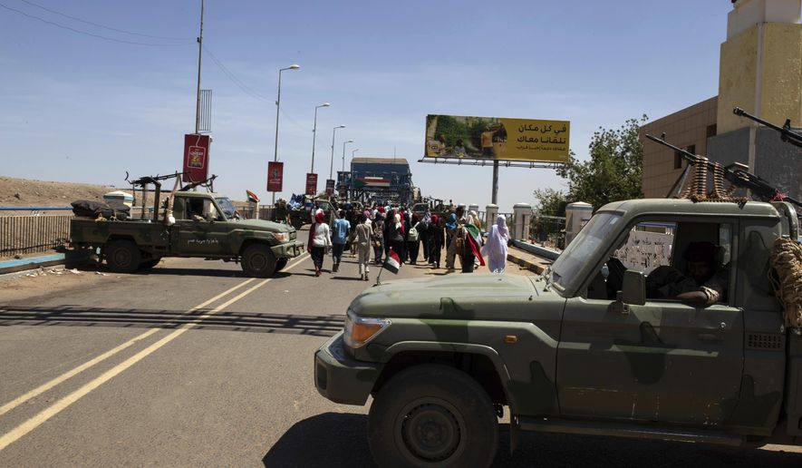 """Demonstrators walk past army vehicles protecting the entrance to a rally near the military headquarters in Khartoum, Sudan, Monday, April 15, 2019. The Sudanese protest movement on Monday welcomed the """"positive steps"""" taken by the ruling military council, which held talks over the weekend with the opposition leaders and released some political prisoners. The praise came despite a brief incident earlier Monday where activists said soldiers attempted to disperse the ongoing protest sit-in outside the military headquarters in the capital, Khartoum, but eventually backed off. (AP Photo/Salih Basheer)"""