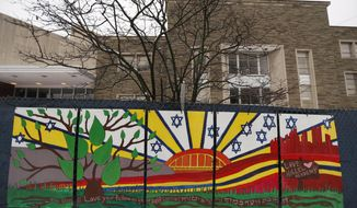 """FILE--This file photo from Feb. 11, 2019 shows artwork on a fence around the Tree of Life Synagogue in Pittsburgh where 11 people were killed and seven others injured during an attack on in October of 2018. The synagogue is inviting young people worldwide to submit artwork in an art project called """"#HeartsTogether: The Art of Rebuilding."""" to cover more of the fencing that surrounds the still-shuttered building. They are looking for """"original, uplifting images and graphics"""" to be printed on windscreens that will cover the temporary perimeter fencing. (AP Photo/Keith Srakocic, File)"""