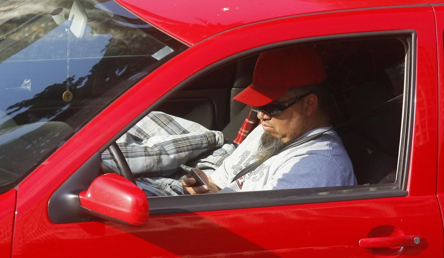 FILE - In this Dec. 14, 2011 file photo, a driver uses a cellphone while driving in Los Angeles. Arizona is one of just three states that has no statewide ban on texting while driving, but that could change this year after a decade of failed attempts in the Legislature to outlaw it. The death of a police officer struck by a driver last Jan. 8, 2019, who was allegedly texting may be a catalyst for lawmakers to change the law. The Senate has passed three bills to punish distracted drivers, but they're held up in the House amid a disagreement among Republicans about how far to go in legislating behavior. (AP Photo/Damian Dovarganes, File)