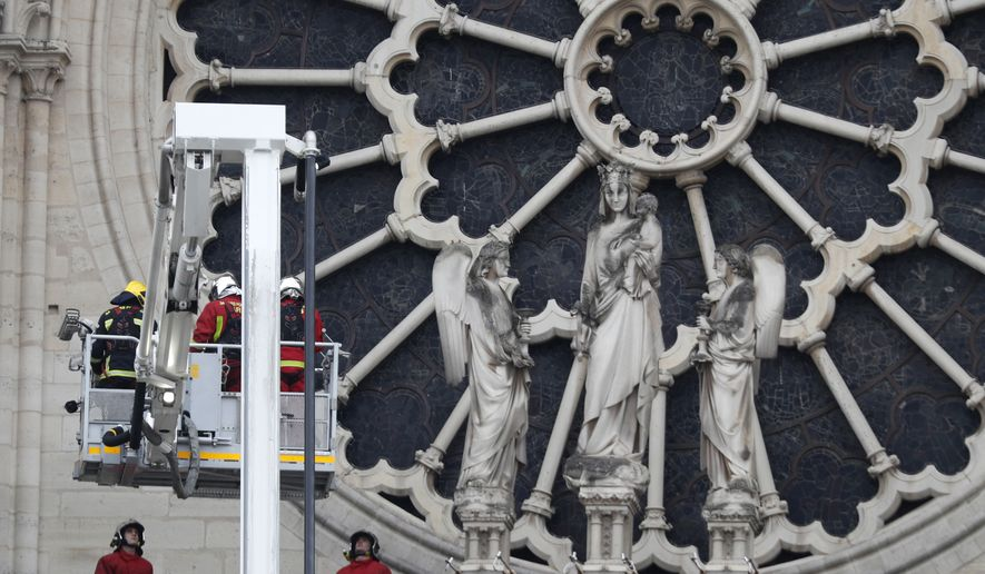 Firefighters work near the rose window of Notre Dame cathedral Tuesday April 16, 2019, following the devastating fire Monday night in Paris.  Experts are assessing the blackened shell of Paris' iconic Notre Dame Cathedral to ascertain what artifacts can be saved and what has been lost in the blaze. (AP Photo/Thibault Camus)