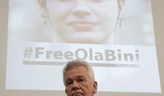The father of detained Swedish programmer Ola Bini, Dag Gustafsson, attends a press conference in Quito, Ecuador, Tuesday, April 16, 2019. The ace Swedish programmer, pictured on the screen in the background, who was an early, ardent supporter of WikiLeaks was arrested in Ecuador last week in an alleged plot to blackmail the country's president over his abandonment of Julian Assange. (AP Photo/Dolores Ochoa)