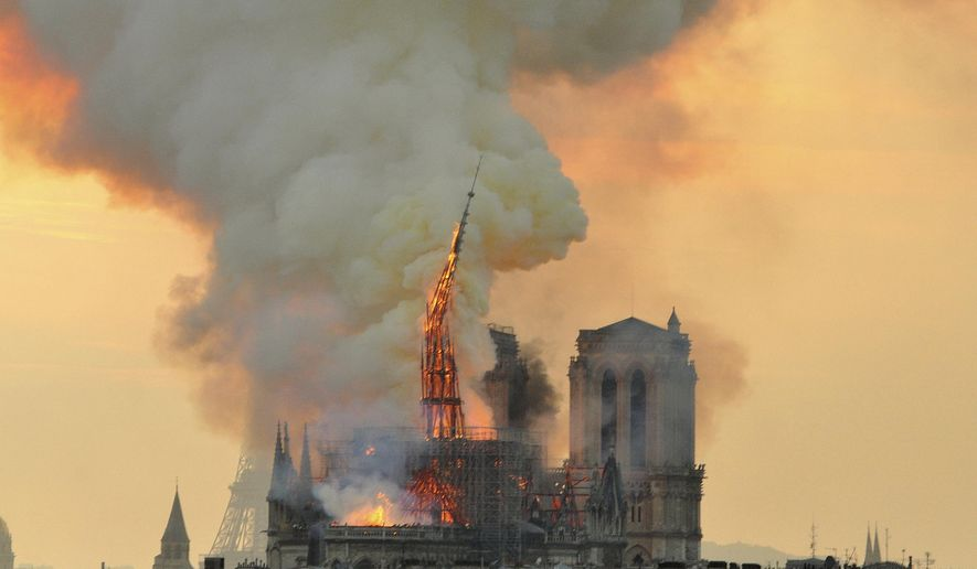 """In this image made available on Tuesday April 16, 2019 flames and smoke rise from the blaze as the spire starts to topple on Notre Dame cathedral in Paris, Monday, April 15, 2019. An inferno that raged through Notre Dame Cathedral for more than 12 hours destroyed its spire and its roof but spared its twin medieval bell towers, and a frantic rescue effort saved the monument's """"most precious treasures,"""" including the Crown of Thorns purportedly worn by Jesus, officials said Tuesday. (AP Photo/Thierry Mallet)"""