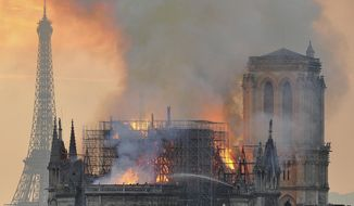 """In this image made available on Tuesday April 16, 2019 flames and smoke rise from the blaze after the spire toppled over on Notre Dame cathedral in Paris, Monday, April 15, 2019. An inferno that raged through Notre Dame Cathedral for more than 12 hours destroyed its spire and its roof but spared its twin medieval bell towers, and a frantic rescue effort saved the monument's """"most precious treasures,"""" including the Crown of Thorns purportedly worn by Jesus, officials said Tuesday. (AP Photo/Thierry Mallet)"""