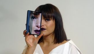 A model holds a Samsung Galaxy Fold smartphone to her face, during a media preview event in London, Tuesday April 16, 2019.  Samsung is hoping the innovation of smartphones with folding screens giving a large interactive space or smaller usual screen, reinvigorates the market. (AP Photo/Kelvin Chan)