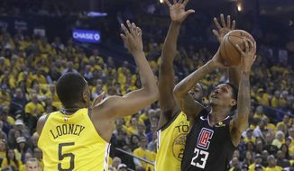Los Angeles Clippers guard Lou Williams (23) shoots against Golden State Warriors center Kevon Looney (5) and forward Draymond Green during the first half of Game 2 of a first-round NBA basketball playoff series in Oakland, Calif., Monday, April 15, 2019. (AP Photo/Jeff Chiu)