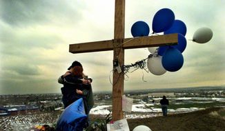 FILE - In this April 24, 1999, file photo, students embrace each other at a makeshift memorial for their slain classmates at Columbine High School on a hilltop overlooking the school in Littleton, Colo. Twelve students and one teacher were killed in a murderous rampage at the school on April 20, 1999, by two students who killed themselves in the aftermath. (AP Photo/Bebeto Matthews, File)