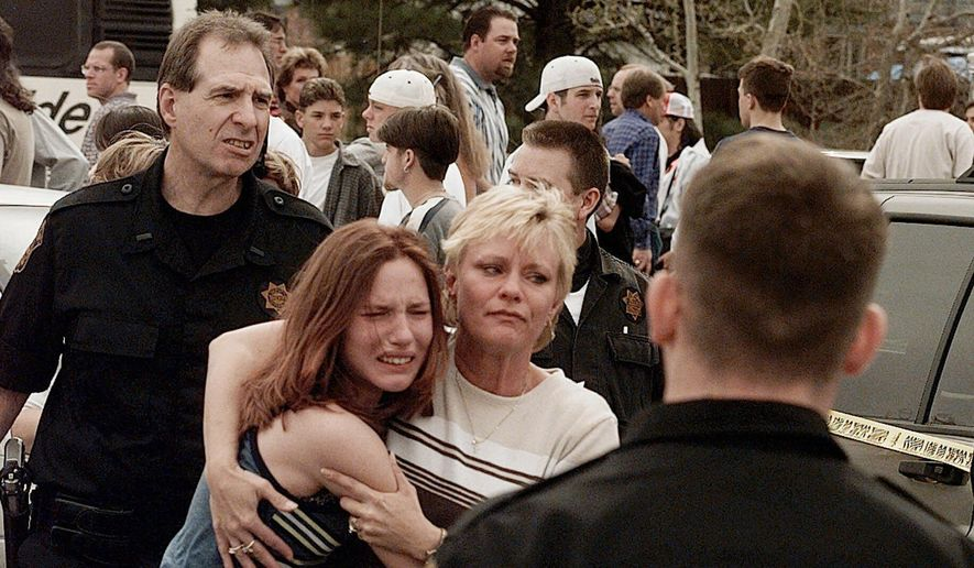 In this April 20, 1999, file photo, a woman embraces her daughter after they were reunited following a shooting at Columbine High School in Littleton, Colo. The shooting shocked the country as it played out on TV news shows from coast to coast. Images from the scene showed terrified students fleeing the school, SWAT officers waiting to enter and an injured boy trying to escape through a window. (AP Photo/Ed Andrieski, File)