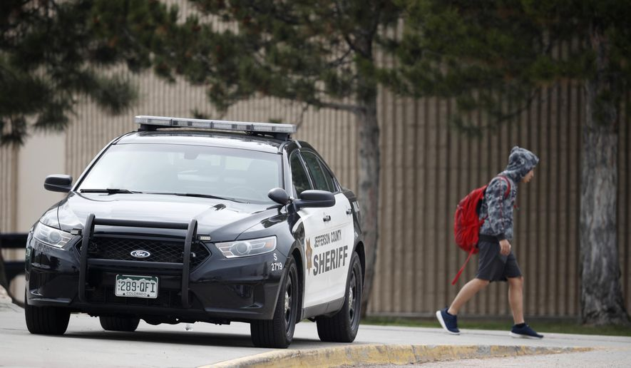 A student leaves Columbine High School late Tuesday, April 16, 2019, in Littleton, Colo. Following a lockdown at Columbine High School and other Denver area schools, authorities say they are looking for a woman suspected of making threats. (AP Photo/David Zalubowski)
