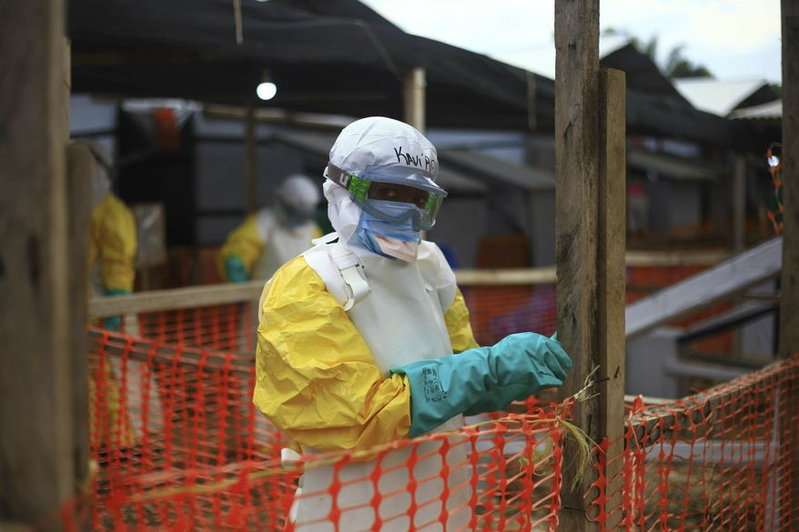 An Ebola health worker is seen at a treatment center in Beni, Eastern Congo, Tuesday April, 16, 2019. Congo's president on Tuesday said he wants to see a deadly Ebola virus outbreak contained in less than three months even as some health experts say it could take twice as long. (AP Photo/Al-hadji Kudra Maliro)