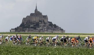 FILE - In this Thursday July 7, 2011 file photo, the pelaton passes the world heritage site Mont Saint-Michel, a rocky tidal island which holds a monastery, during he sixth stage of the Tour de France cycling race. Monuments are the emotional backbone of France. That accounts for the despair over a blaze that killed no one, yet seared the collective soul. It is the power Notre Dame had _ still has, despite the charred scars on its Gothic walls.  (AP Photo/Laurent Cipriani, File)