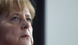 German Chancellor Angela Merkel looks up during joint press conference with the President of Ukraine, Petro Poroshenko, as part of a meeting at the chancellery in Berlin, Germany, Friday, April 12, 2019. (AP Photo/Michael Sohn)