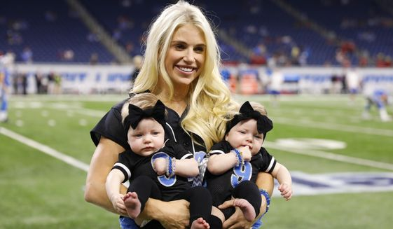 In this Sept. 24, 2017, file photo, Kelly Stafford, wife of Detroit Lions quarterback Matthew Stafford, holds the couple's twins Sawyer, left, and Chandler during pre-game of an NFL football game against the Atlanta Falcons, in Detroit. Kelly Stafford plans to have surgery to remove a brain tumor. Stafford shared the details Wednesday, April 3, 2019, on her Instagram account. She says an MRI showed the tumor on cranial nerves after she had vertigo spells within the last year. (AP Photo/Rick Osentoski, File)